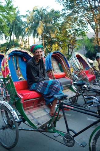 Rickshaws line the streets of Dhaka waiting for the post-office crowd. Amidst the rush and the orchestra of city sounds is a radiant smile as bright and shiny as the colors of Bangladesh.