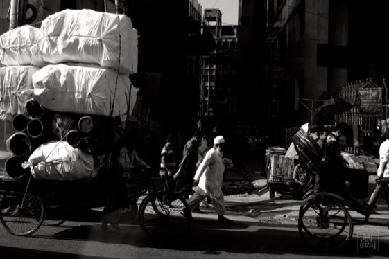 A man, a rickshaw and a mountain of barrels crossing the busy streets of Dhaka amidst the traffic.